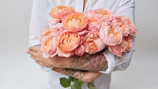 Kobieta z tatuażem na rękach trzymająca bukiet różowych róż, walentynki