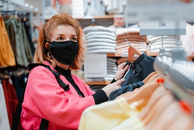 Kobieta z telefonem jasny różowy płaszcz na zakupy z czarną maską ochronną na twarzy przed zainfekowanym wirusem powietrzem.