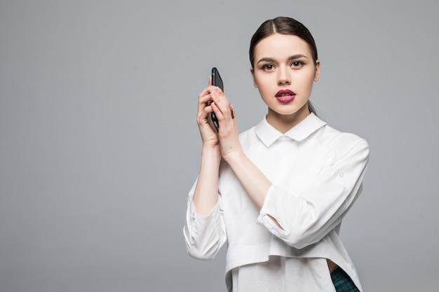 Kobieta z telefonem komórkowym. na białym tle na białej ścianie.