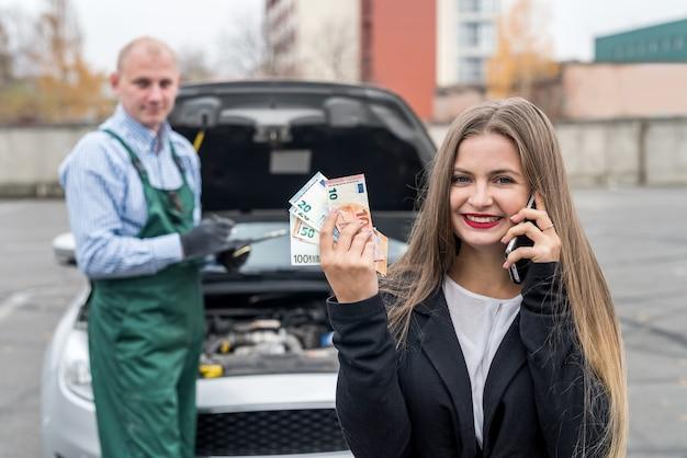 Kobieta z telefonem komórkowym, samochodem i mechanikiem