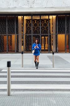 Kobieta z telefonem komórkowym w mieście na przejściu dla pieszych
