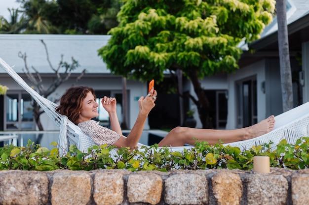 Kobieta z telefonem odpoczywa leżąc na hamaku z telefonem komórkowym