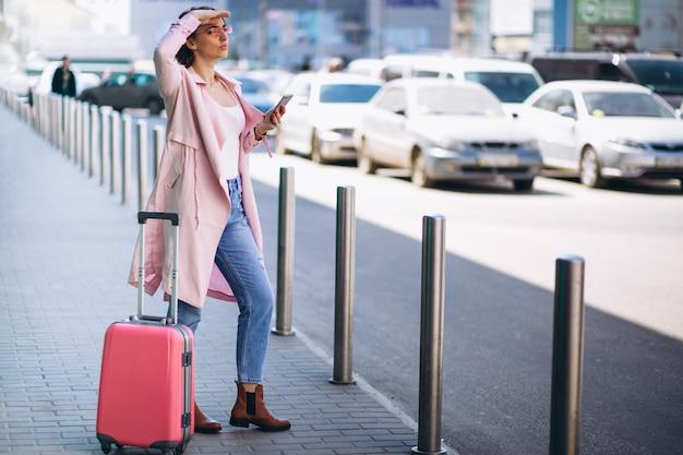Kobieta z telefonem przy lotniskiem