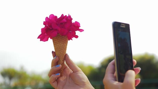 Kobieta z telefonem robi zdjęcie bukietu kwiatów w kształcie stożka