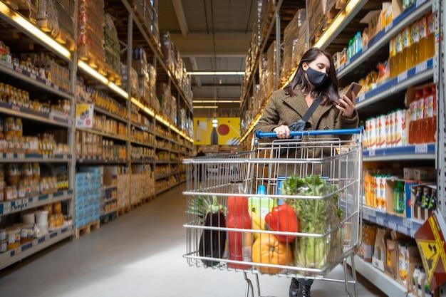 Kobieta z telefonem sprawdza aplikację listy zakupów w sklepie spożywczym kopia przestrzeń