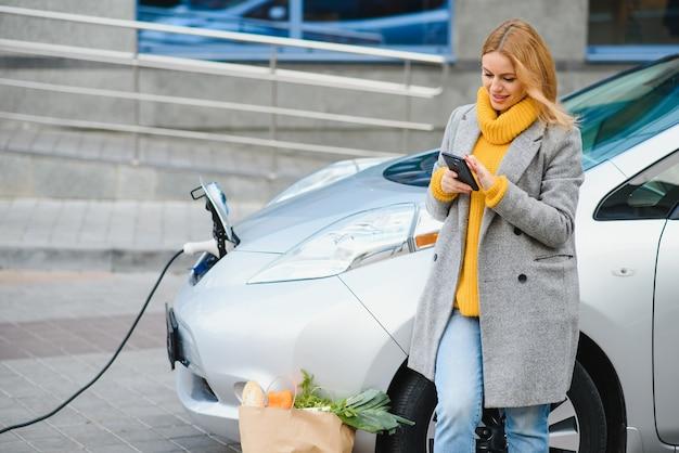 Kobieta z telefonem w pobliżu wypożyczalni samochodów elektrycznych