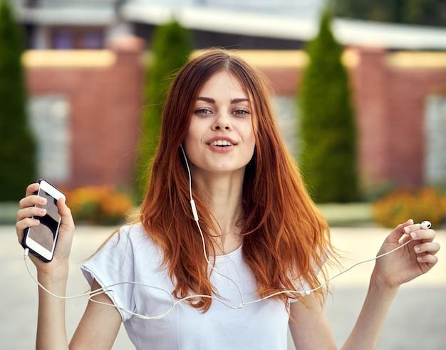 Kobieta z telefonem w słuchawkach działa