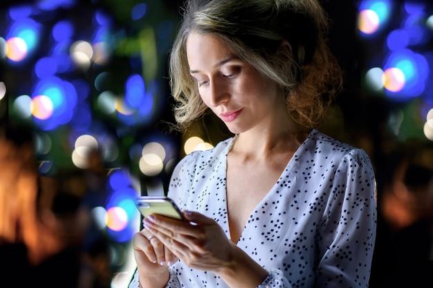 Kobieta z telefonu w nocy portret miasta zaświeca bokeh.