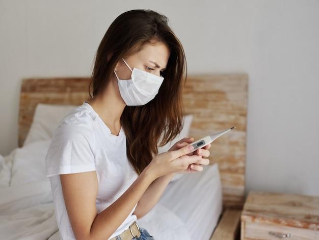 Kobieta z termometrem w rękach w sypialni podczas badania stanu zdrowia maski medycznej