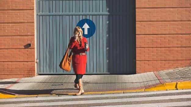 Kobieta z termosem i smartphone skrzyżowania ulicy