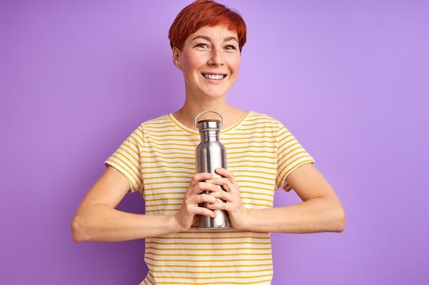 Kobieta z termosem na białym tle na fioletowej ścianie, młoda kobieta w codziennym stroju świeci szczęściem, uśmiechem