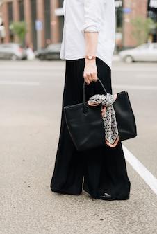Kobieta z torbą na tle miasta