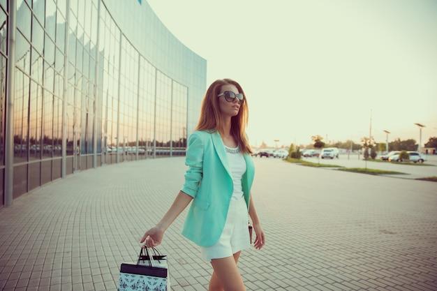 Kobieta z torbą na zakupy idzie wzdłuż sklepu