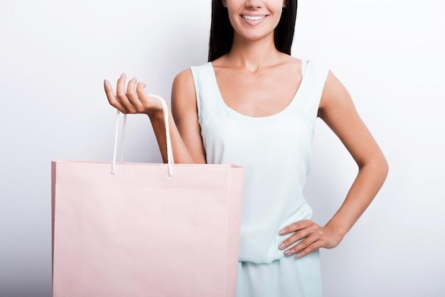 Kobieta z torbą na zakupy. przycięty obraz wesołej młodej kobiety w sukience stojącej na białym tle i niosącej torbę na zakupy