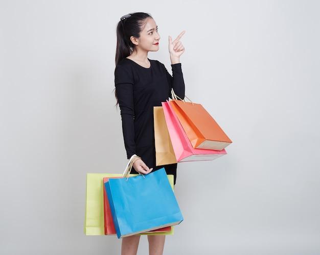 Kobieta z torba na zakupy stoi na bielu