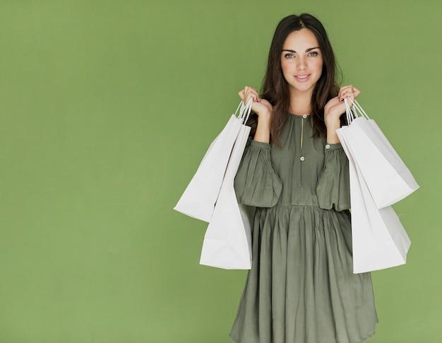 Kobieta z torba na zakupy w oba rękach na zielonym tle