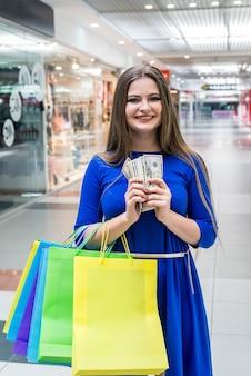Kobieta z torbami na zakupy i banknotami dolarowymi