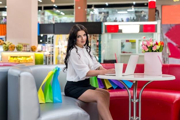 Kobieta z torbami na zakupy i laptopem w kawiarni