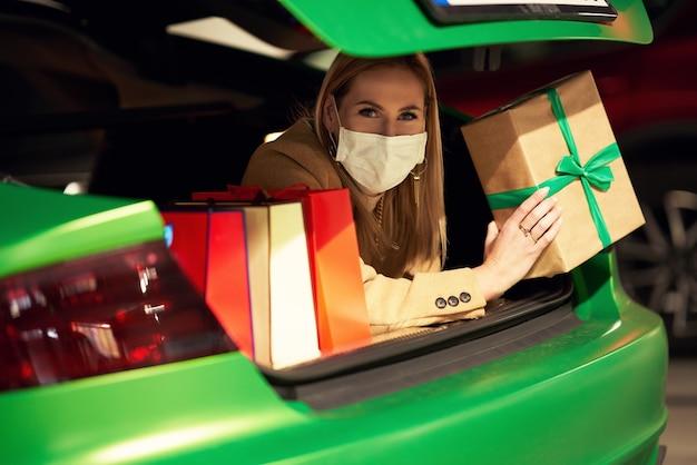 Kobieta z torbami na zakupy i prezentami świątecznymi w masce i leżąca w bagażniku na parkingu