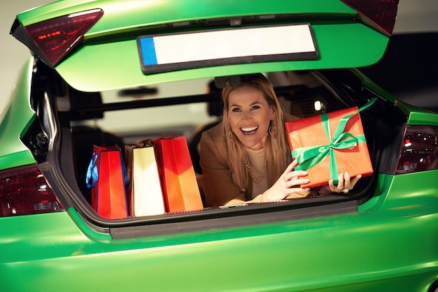 Kobieta z torbami na zakupy i świątecznymi prezentami leżącymi w bagażniku na parkingu