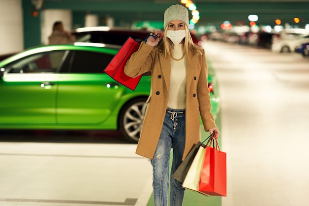 Kobieta z torbami na zakupy w masce na podziemnym parkingu