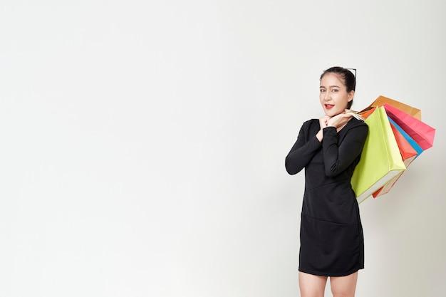 Kobieta z torby na zakupy biała ściana