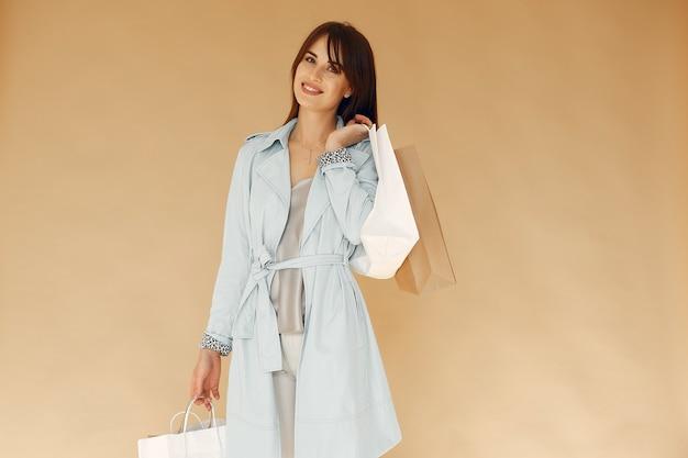 Kobieta z torby na zakupy. dama na beżowej ścianie. kobieta w niebieskiej kurtce.