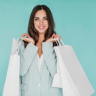 Kobieta z torby na zakupy w obu rękach pozuje do kamery