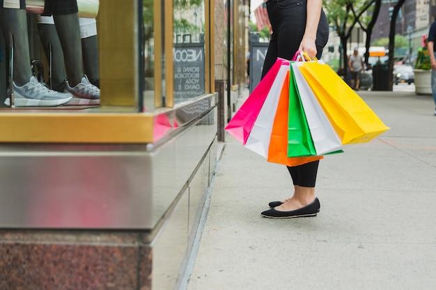 Kobieta z torby na zakupy w pobliżu okna sklepu