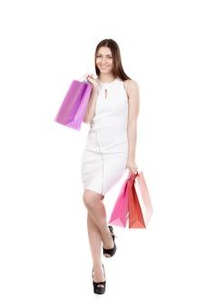 Kobieta z torby zakupu i jedną nogą podniesione