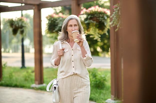 Kobieta z torebką pije kawę w parku