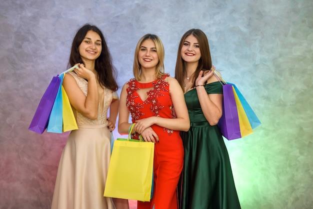Kobieta z torebkami na prezenty na imprezie sylwestrowej pozuje w eleganckich sukniach wieczorowych