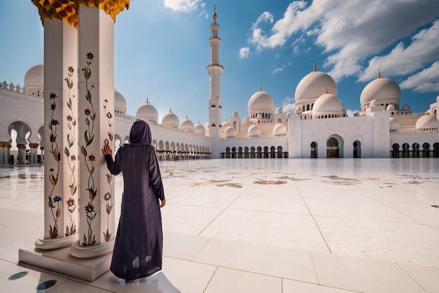 Kobieta z tradycyjną sukienką wewnątrz meczetu sheikh zayed. abu zabi, zjednoczone emiraty arabskie.