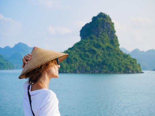 Kobieta z tradycyjnym wietnamczyka kapeluszowym patrzeje unikalnym widokiem halong zatoka, wietnam. turysta podróżujący na rejs wśród skał ha long bay na szczyt.