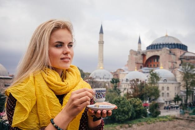 Kobieta z turecką kawą na hagia sophia bacground, istanbuł