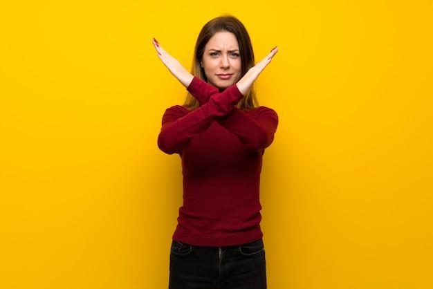 Kobieta z turtleneck nad żółtej ścianie robi żadny gestowi