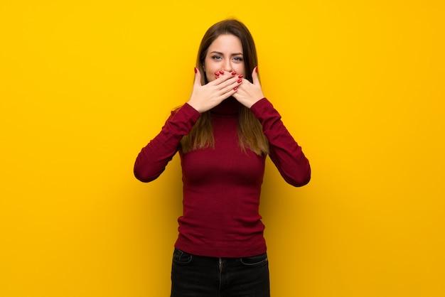 Kobieta z turtleneck nad żółtym ściennym nakrywkowym usta z rękami dla mówić coś nieodpowiedniego