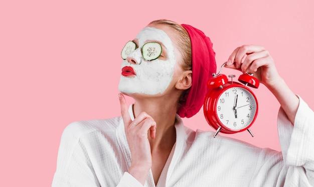 Kobieta z twarzową maską na twarzy i budzikiem w ręku. maska kosmetyczna. zabieg upiększający. terapia uzdrowiskowa