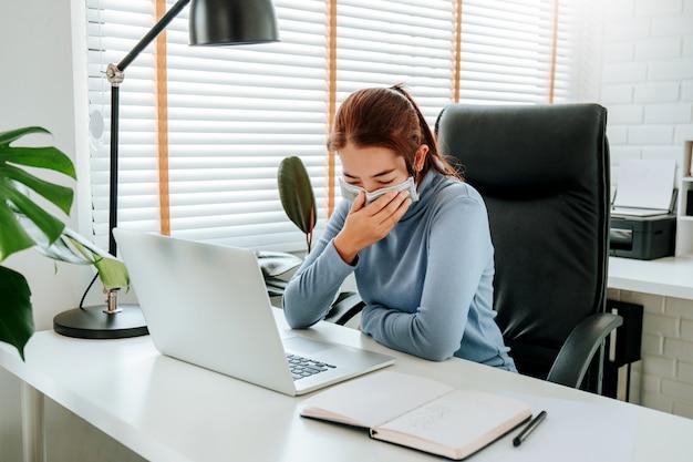 Kobieta z twarzy maski obsiadaniem na biurowym biurku w domu