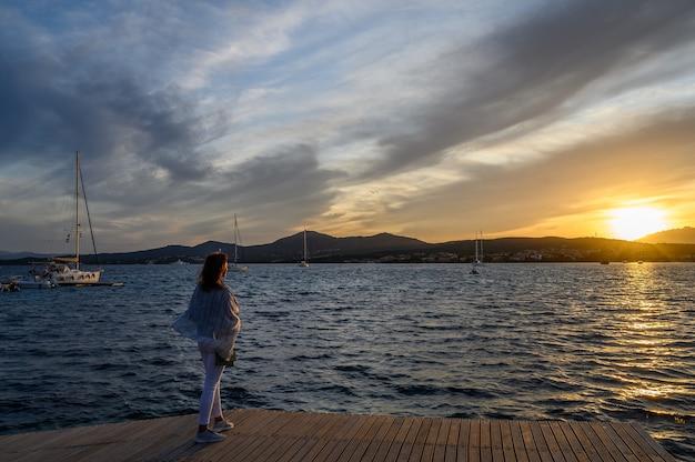 Kobieta z tyłu stoi na molo i patrzy na zachód słońca na tle gór nad morzem