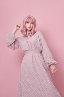Kobieta z ufarbowanymi na różowo włosami w długiej sukni. portret dziewczynki z farbowaniem włosów na różowej ścianie. idealna fryzura i układanie włosów