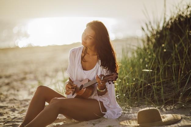 Kobieta z ukulele na plaży letnie wakacje