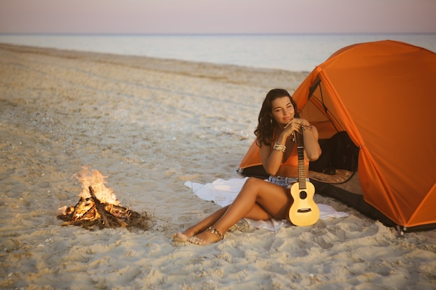 Kobieta z ukulele z pomarańczowym namiotem na letnie wakacje na plaży