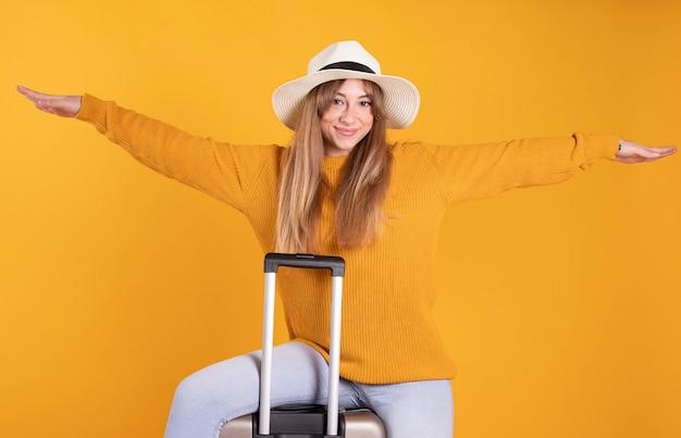 Kobieta z walizką i kapeluszem, podróży pojęcie, kolor żółty przestrzeń