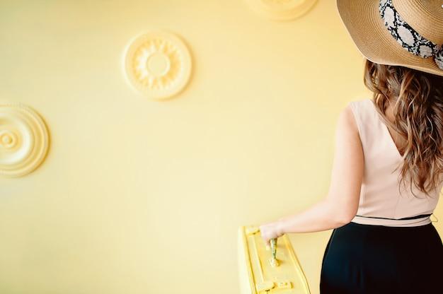 Kobieta z walizką i kapeluszem
