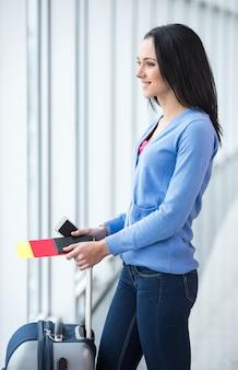 Kobieta z walizką i paszportem jest gotowa do podróży.
