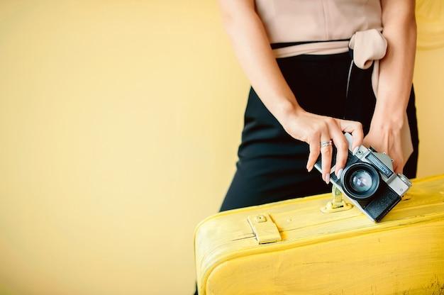 Kobieta z walizką i rocznika kamerą