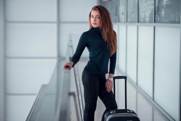 Kobieta z walizką pozuje na przeszklonym balkonie.