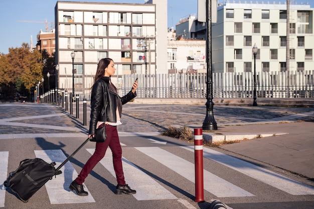 Kobieta z walizką spaceruje i konsultuje telefon