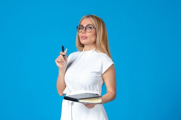 Kobieta z widokiem z przodu w białej sukni pozuje z notatnikiem na niebieskiej pracy